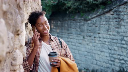 плед : Millennial black woman with short curly hair wearing a plaid shirt leaning on stone wall talking on smartphone and drinking a takeaway coffee, selective focus Стоковые видеозаписи