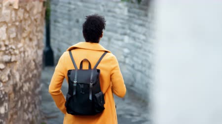 šik : Back view of young woman wearing a yellow coat walking away from camera down an alleyway between stone walls, selective focus