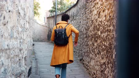 groch : Back view of young black woman wearing a yellow pea coat putting smartphone in the back pocket of her jeans and walking away from camera down a narrow alleyway between stone walls, selective focus Wideo