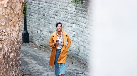 плед : Front view of young black woman wearing a yellow pea coat holding a takeaway coffee walking towards camera in an alleyway between stone walls, elevated view