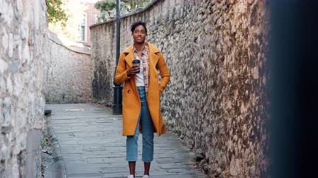 wearing earphones : Front view of young black woman wearing a yellow pea coat drinking a takeaway coffee walking in an alleyway between old stone walls, selective focus Stock Footage