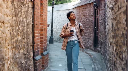 baixo : Young woman wearing a plaid shirt and blue jeans walking towards camera in an alley between old stone walls holding a takeaway coffee, selective focus