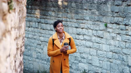 selektif : Millennial black woman wearing a yellow pea coat walking in an alleyway in a historical district holding a takeaway coffee, selective focus Stok Video