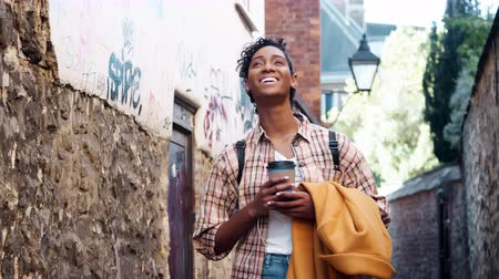 focus on foreground : Young black woman wearing a plaid shirt standing in an alleyway holding her coat and a takeaway coffee, smiling to camera, close up