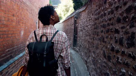 плед : Millennial black woman wearing a plaid shirt carrying a backpack walking in a narrow alleyway in a historical district and looking around, back view, follow shot