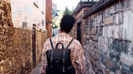 focus on foreground : Young black woman with a backpack walking in a narrow alleyway between stone walls, back view, follow shot Stock Footage