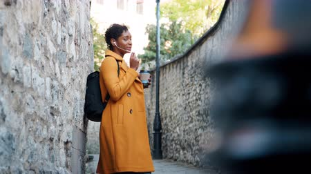 wearing earphones : Young adult woman wearing a yellow pea coat talking using her smartphone earphones and drinking a takeaway coffee, leaning on a stone wall in a historical alleyway, low angle, rack focus Stock Footage