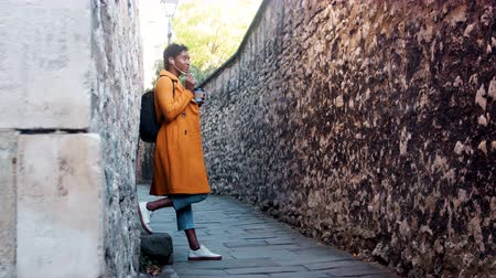 ângulo : Young woman wearing a yellow pea coat and blue jeans leaning on stone wall in an alleyway talking on her smartphone using earphones, low angle, full length