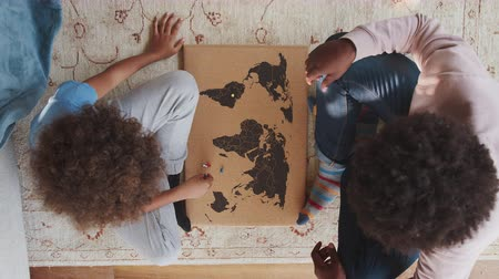 naproti : Close up overhead view of a mixed race pre teen boy and his father sitting cross legged on the floor opposite each other playing an educational game with a world map and map pins