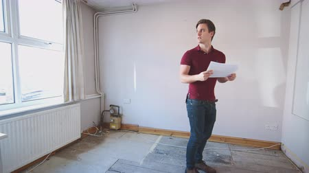 immobilien : Male First Time Buyer Looking At House Survey In Room To Be Renovated