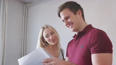 immobilien : Couple Buying House For First Time Looking At House Survey In Room To Be Renovated