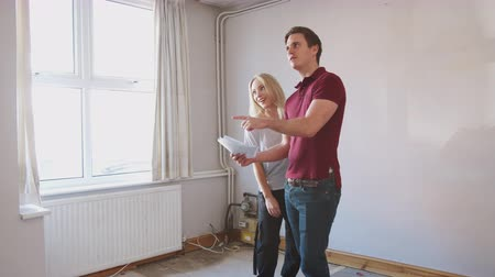 harmincas : Couple Buying House For First Time Looking At House Survey In Room To Be Renovated
