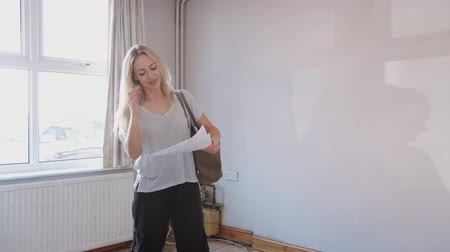 immobilien : Female First Time Buyer Looking At House Survey In Room To Be Renovated