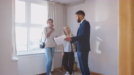 três pessoas : Two Female Friends Buying House For First Time Looking At House Survey With Realtor
