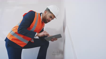immobilien : Surveyor In Hard Hat And High Visibility Jacket With Digital Tablet Carrying Out House Inspection Stockvideo
