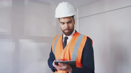 immobilien : Portrait Of Surveyor In Hard Hat And High Visibility Jacket With Digital Tablet Carrying Out House Inspection Stockvideo