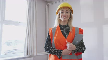 immobilien : Portrait Of Female Surveyor In Hard Hat And High Visibility Jacket With Digital Tablet Carrying Out House Inspection Stockvideo