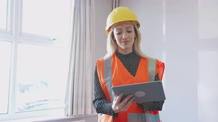 жесткий : Female Surveyor In Hard Hat And High Visibility Jacket With Digital Tablet Carrying Out House Inspection