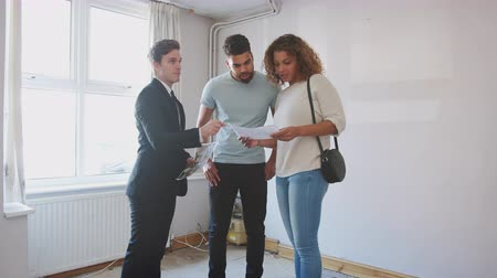 immobilien : Couple Buying House For The First Time Looking At Survey With Realtor