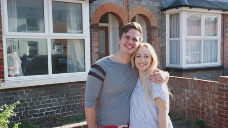 harmincas : Portrait Of Young Couple Standing Outside New Home In Urban Street
