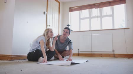 harmincas : Couple Sitting On Floor Looking At Floor Plans In Empty Room Of New Home Stock mozgókép
