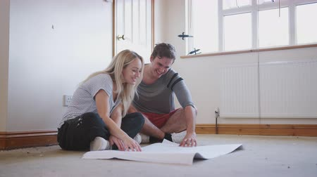 primeiro plano : Couple Sitting On Floor Looking At Floor Plans In Empty Room Of New Home Stock Footage