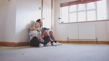 harmincas : Couple Sitting On Floor In Empty Room Of New Home Planning Design