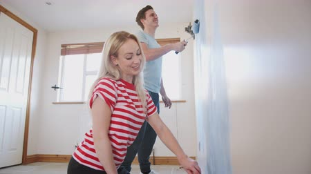 harmincas : Couple Decorating Room In New Home Painting Wall Together