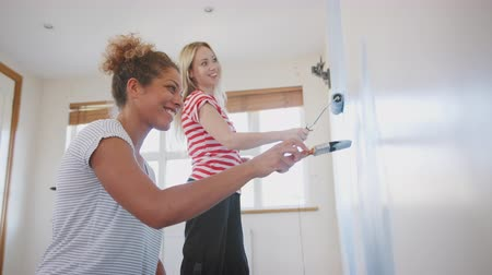 handheld shot : Two Women Decorating Room In New Home Painting Wall Together Stock Footage