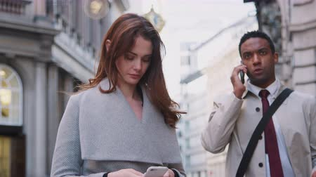 dojíždění : Millennial white woman standing on the street using smartphone, young black businessman talking on phone walking past, close up, low angle