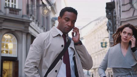 dojíždění : Young black businessman standing on street talking on smartphone, white millennial woman walking past also using phone, close up, low angle