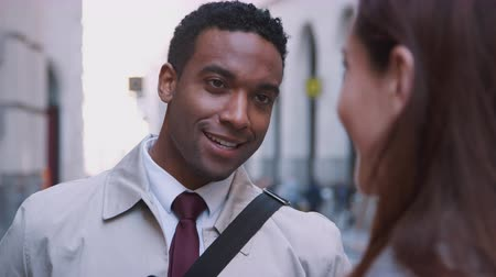 etnia africano : Millennial black businessman standing in the street listening his white female colleague talking, close up, selective focus Stock Footage