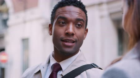 harmincas : Millennial black businessman standing in the street talking with his white female colleague, close up, selective focus