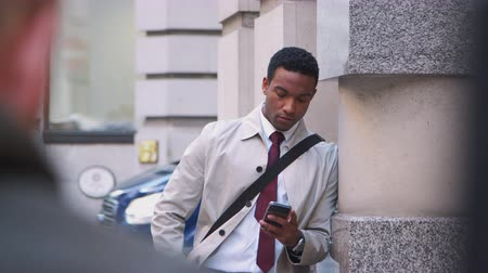 harmincas : Young black businessman leaning on a wall in the street in London using his smartphone, selective focus, waist up
