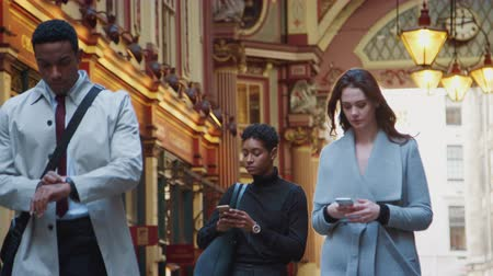 dojíždění : Millennial business people walking towards camera in London's historical Leadenhall covered street market, checking the time and using their phones, low angle