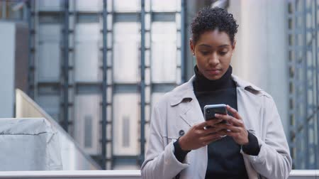Лондон : Close up of fashionable young black woman standing in the city in front of a modern building using her smartphone, front view, waist up