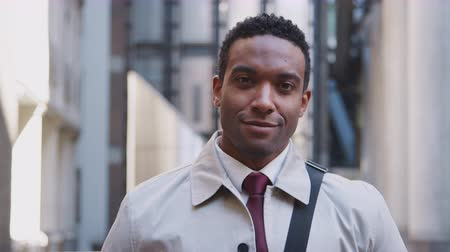 город : Confident young black businessman standing on the street and smiling to camera, focus on foreground, close up