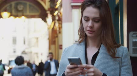 conveniência : Young white businesswoman standing on a busy London street using her smartphone, close up, selective focus Vídeos