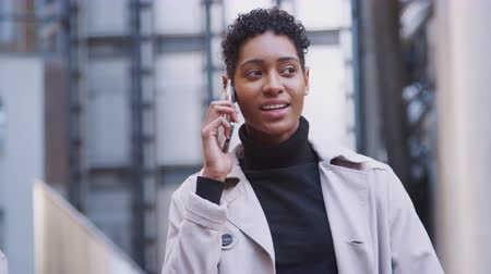 Лондон : Fashionable young black woman standing in a business area of the city talking on her smartphone, close up, focus on foreground Стоковые видеозаписи