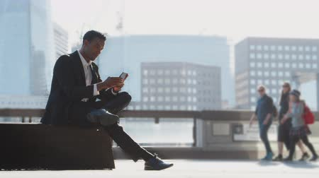 harmincas : Millennial black businessman wearing a suit and a white shirt sitting on the River Thames embankment using his smartphone, full length