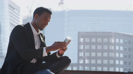 etnia africano : Close up of millennial black businessman wearing a suit and a white shirt sitting on the River Thames embankment using his smartphone, close up