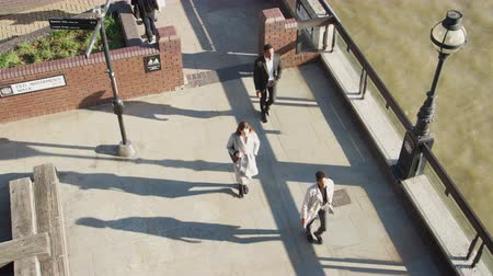 harmincas : Elevated view of three city workers walking on a sunny urban street by the River Thames in the City of London, lockdown