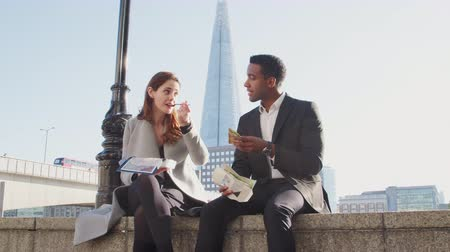 londyn : Two millennial colleagues take a break on the embankment eating and talking sitting on the Thames wall by the river near London Bridge, low angle, close up