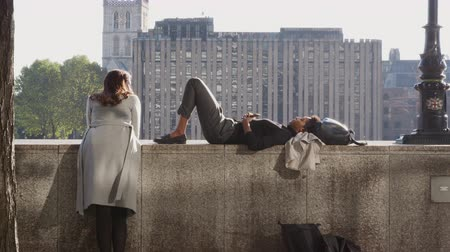 focus on foreground : Black millennial woman lying on the embankment wall by the Thames in the City of London, talking with her friend, backlit