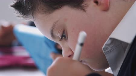 elsődleges : Schoolboy with Down Syndrome using stylus and tablet in a primary school class, close up, side view Stock mozgókép