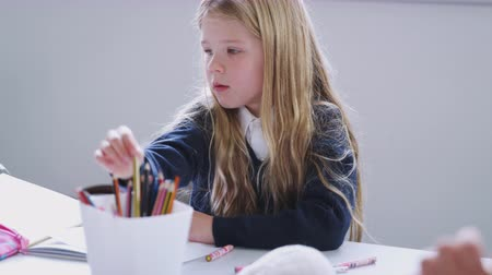 atenção : A schoolgirl sitting at a table in a primary school class drawing, front view, selective focus