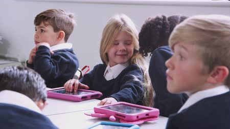 five : Primary school children sitting at a table in a classroom with tablet computers, selective focus