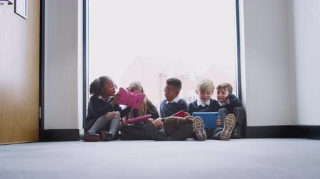 v řadě : Five primary school kids sitting on the floor in a school corridor using tablet computers, low angle