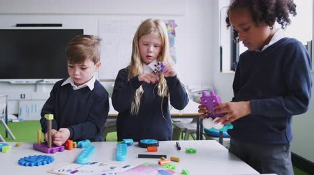 três pessoas : Three primary school children working together with construction blocks in a classroom, front view Vídeos