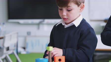 pré adolescente : A schoolboy constructing a toy in a primary school classroom, close up, focus on foreground Vídeos